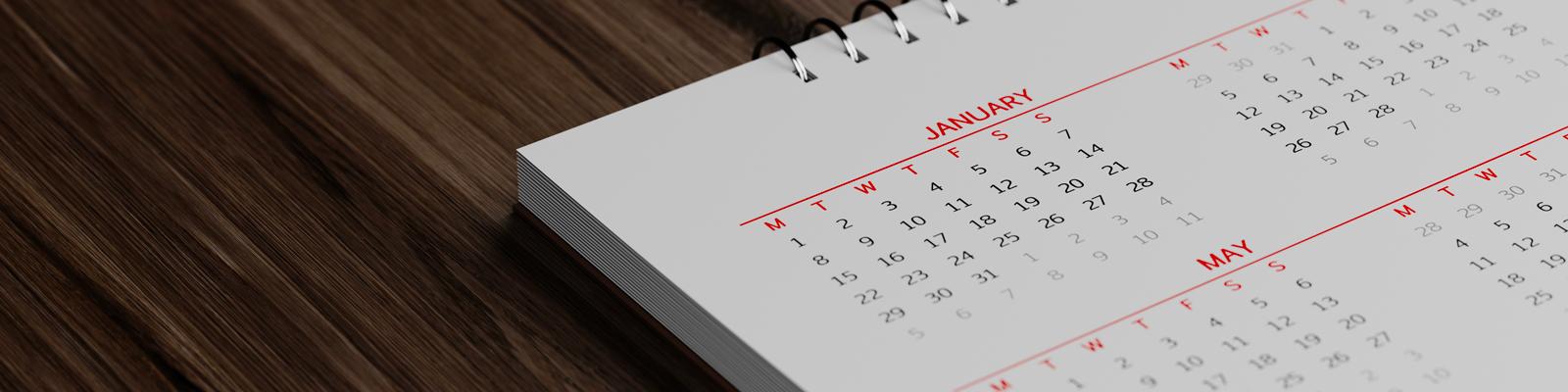 A closeup of a calendar year sitting on a wooden desktop